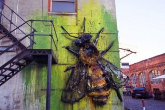 A giant bee on wall in Lisbon made entirely from waste